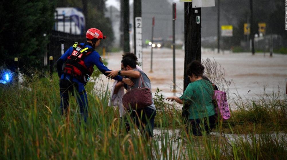 一名救援人员帮助居民穿越悉尼西部的一条被水淹没的街道。.jpg
