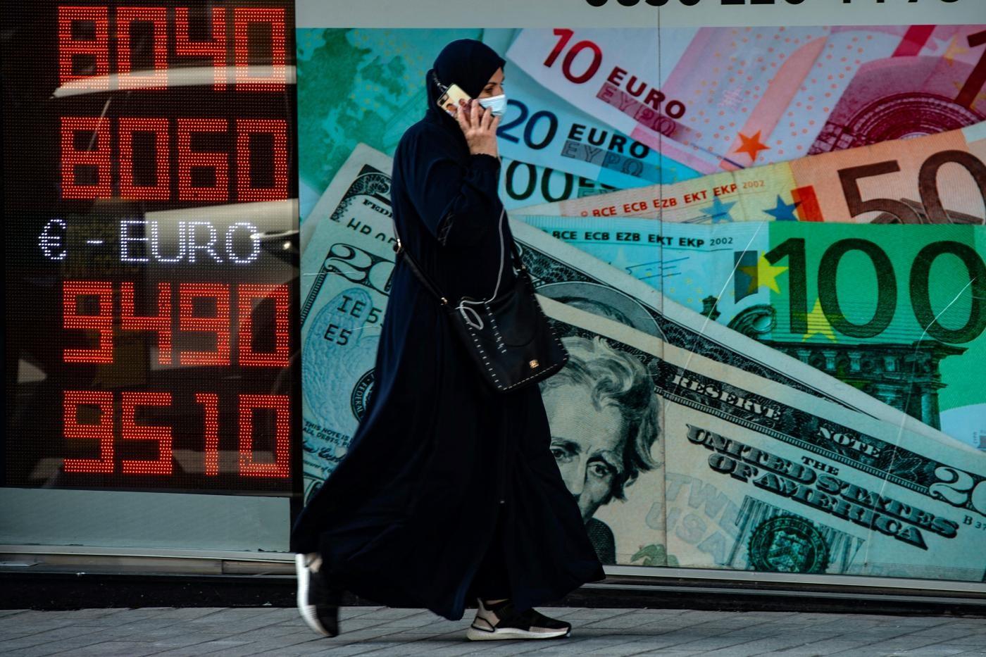 2020年10月26日,一名妇女走过一块显示外汇汇率的显示屏(法新社).jpg