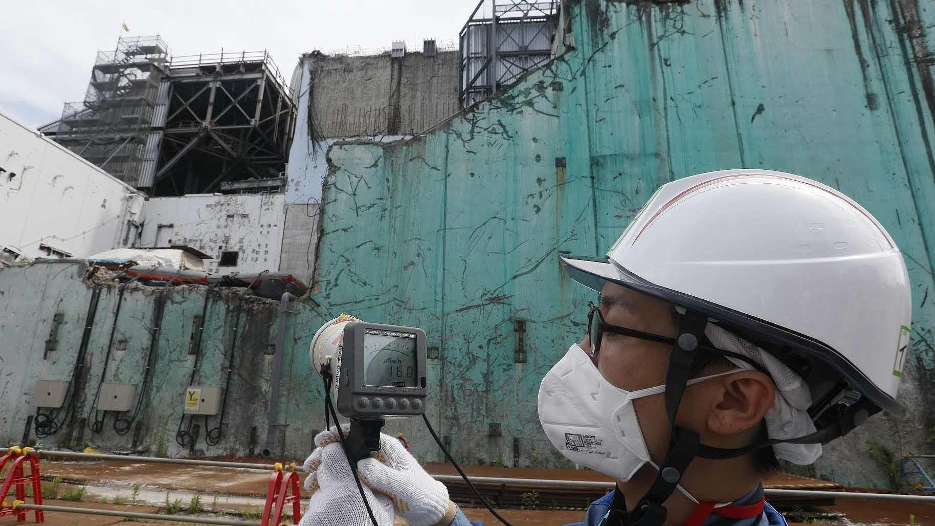 东京电力公司的一名工作人员在2018年7月27日测量日本福岛核电站的辐射水平。.jpeg